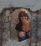 Judy peeks from a rock window along Lands End Trail