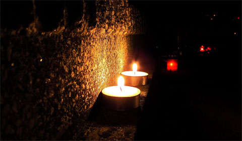 Graveyards lit by hundreds of candles make the night feel magical