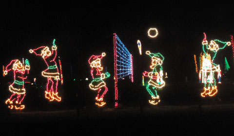 The elves play beach volleyball while Santa surfs