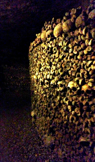 In the depths of the Catacombs below Paris. Millions of bones, neatly arranged.