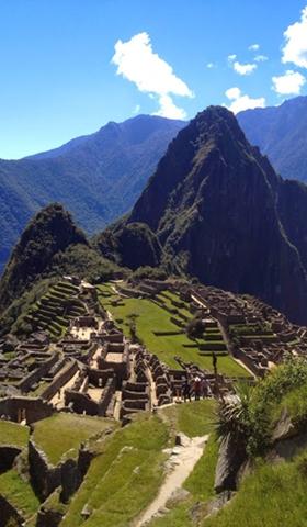 Machu Picchu ruins with the dark Huayna Picchu mountain.